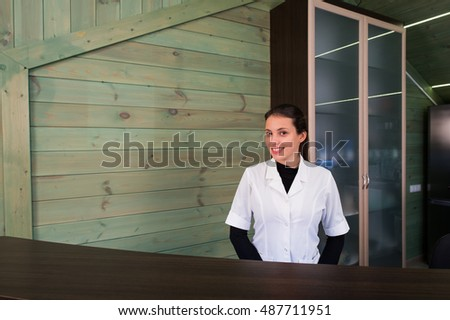 Woman on receptrion smiles and welcomes the virtual visitor at spa or modern clinic. Papers with agreement in your hand.
