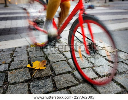 Woman on red bike in blurred motion in autumn - stock photo