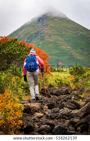 Woman on rocky path among autumn colors on hiking trail in Daisetsuzan National Park, Hokkaido, Japan.