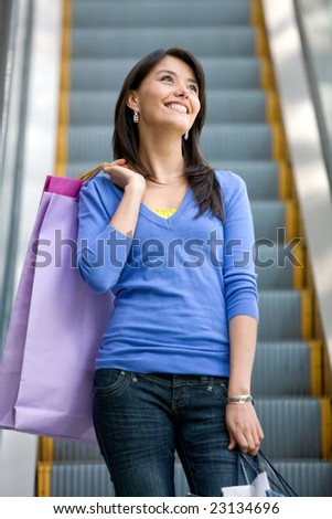 Woman on scalators in a shopping mall holding some bags