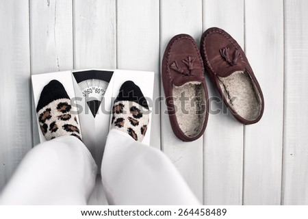 Woman on scale in casual clothes - stock photo