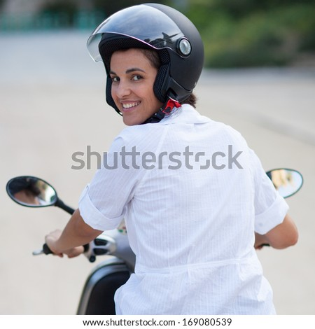Woman on scooter rear view - stock photo