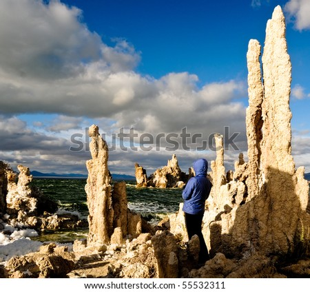 Woman on shore of Mono Lake in a gallery of Tufa formations