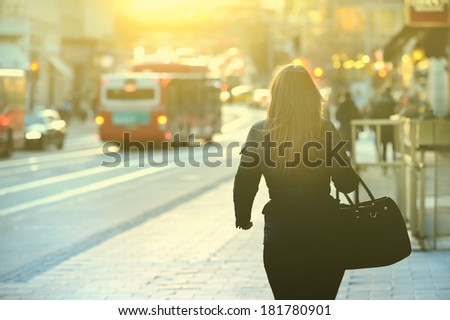 Woman on sidewalk in the absolute sunset - stock photo