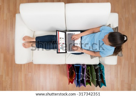 Woman On Sofa With Shopping Bags Browsing Shopping Site On Laptop - stock photo