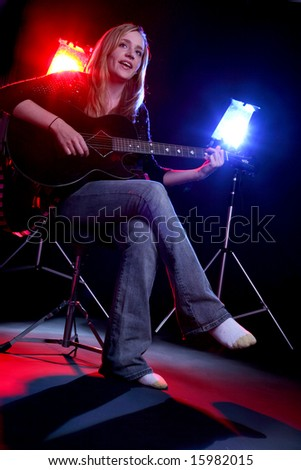 woman on stage playing guitar - stock photo