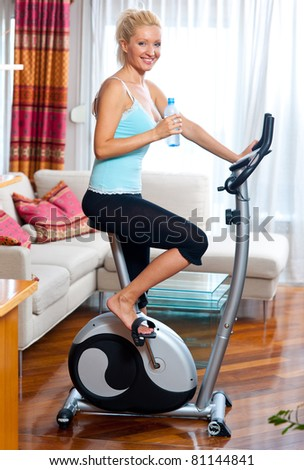 woman on stationary bicycle with water bottle in her home relaxing - stock photo