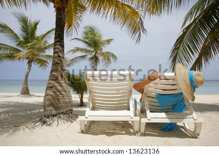Woman on sun lounger surrounded by coconut palm trees - stock photo