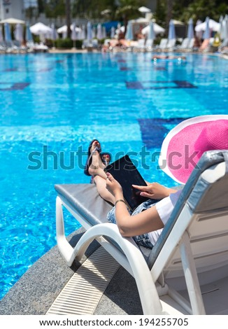woman on sunbed waering beautiful pink hat