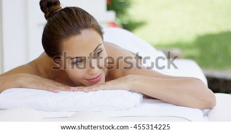 Woman on table with hair up in a bun smiles - stock photo