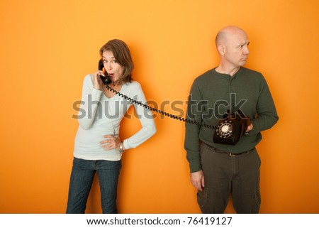 Woman on telephone call with unhappy man holding the phone - stock photo