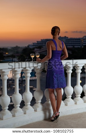 Woman on the balcony with two glasses of wine