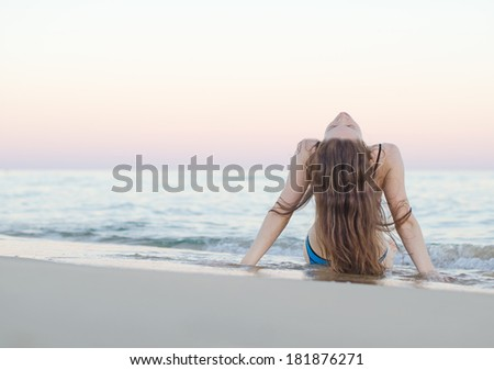 Woman on the beach at sunset. - stock photo