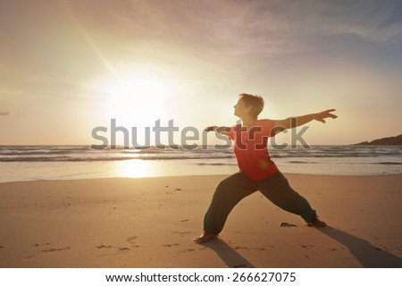 woman on the beach doing fitness, on sunrise - stock photo
