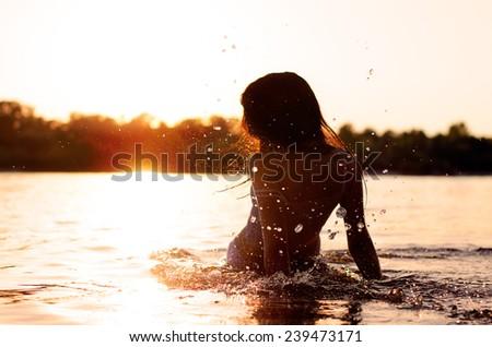 Woman on the beach enjoys the sun - stock photo