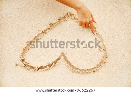 woman on the beach making heart on the sand - stock photo