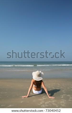 Woman on the beach near sea and blue sky - stock photo