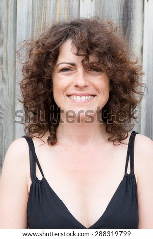Woman on the beach smiling with freckles and curly hair - stock photo