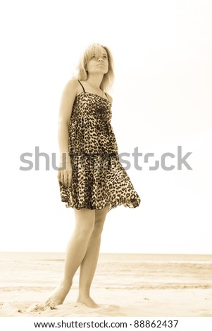 woman on the beach watching into the distance - stock photo