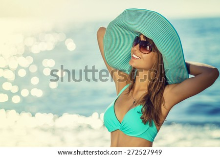 Woman on the beach wearing a hat. Young sexy woman relaxing and smiling on a beach near a blue sunny sea. Eternal summer concept. - stock photo