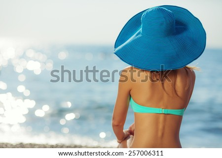 Woman on the beach wearing a hat. Young sexy woman relaxing on a beach near a blue sunny sea. Eternal summer concept.  - stock photo