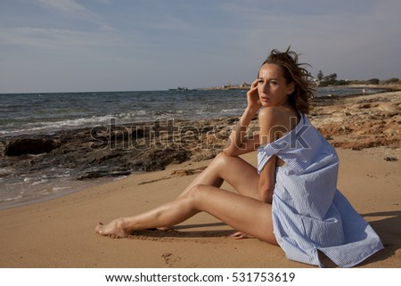 Woman on the beach wearing only shirt
