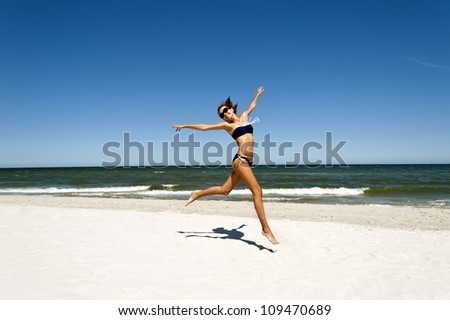 Woman on the beach with joy on her face - stock photo