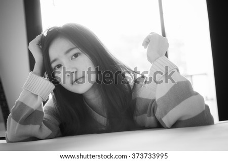 Woman on the bed in the bedroom. Back and white image - stock photo