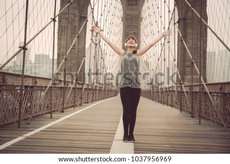 Woman on the Brooklyn bridge with arms raised