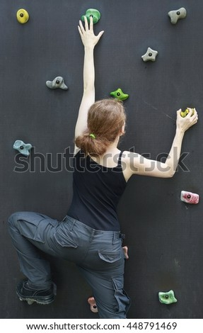 Woman on the climbing wall - stock photo