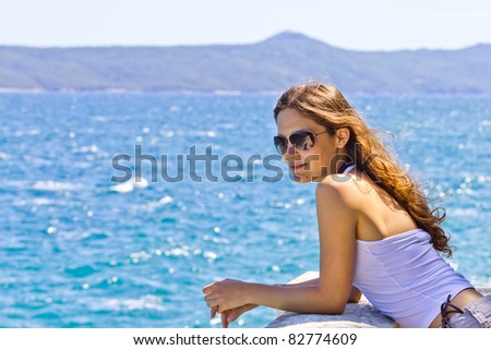 Woman on the deck by the sea - stock photo