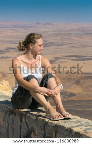 woman on the edge of the cliff on the background of the desert - stock photo