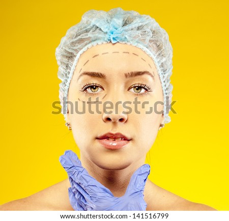 woman on the examination, the doctor. before plastic surgery. yellow background - stock photo