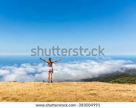 Woman on the mountain peak - stock photo