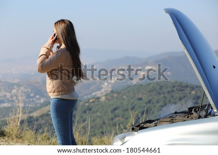 Woman on the phone asking for assistance beside her crashed breakdown car in a mountain road - stock photo