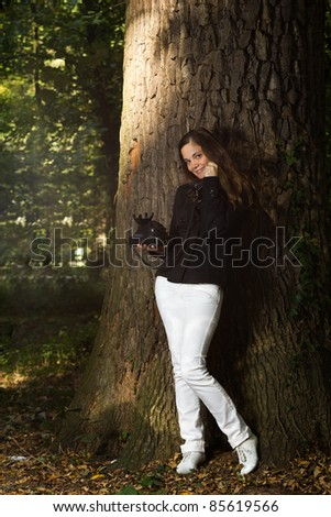 Woman on the phone in the woods - stock photo