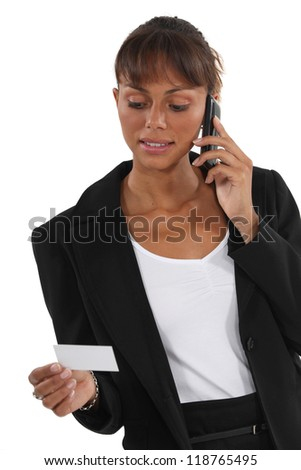 Woman on the phone watching business card - stock photo