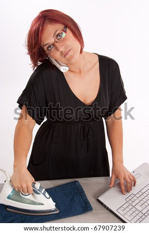Woman on the phone, while ironing and using a computer - stock photo