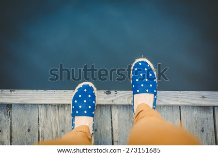 woman on the pier takes a step into the water, from above - stock photo