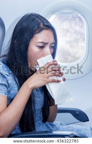 Woman on the plane vomited in a paper bag. Traveler in a flying aircraft has nauseous. Nausea passenger in a flying airplane. Turbulence on the plane. - stock photo