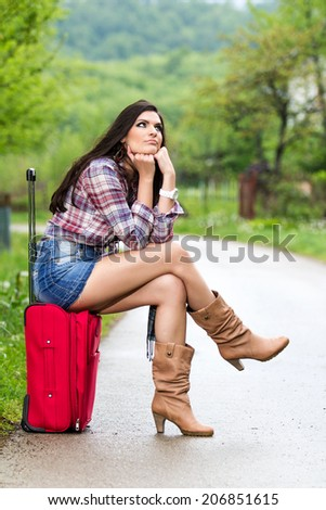 Woman on the road sitting on her suitcase under the blue sky.