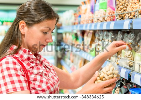 woman on the shelf at the store chooses the nuts - stock photo