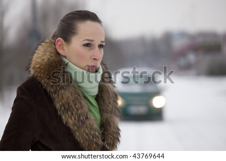 woman on the snowy road - car in background - stock photo