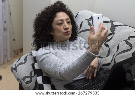 woman on the sofa with computer and mobil - stock photo