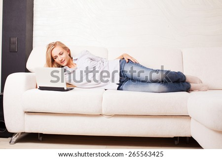 Woman on the sofa with laptop. Happy female with computer at hame - stock photo