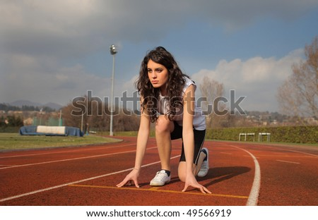 Woman on the starting grid of a running track - stock photo