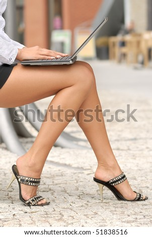 woman on the street sitting with a laptop computer in her lap and typing - stock photo