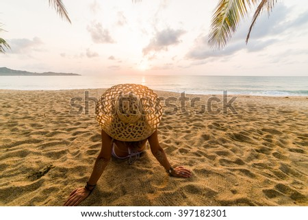 Woman on the tropical beach at sunset under the coconut trees - stock photo