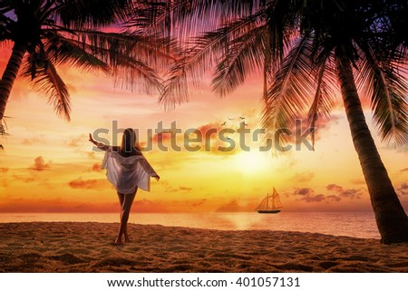 Woman on the tropical beach at sunset under the coconut trees at the resort - stock photo