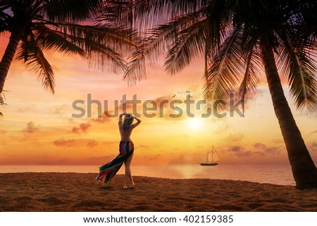 Woman on the tropical beach at sunset under the coconut trees at the resort